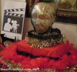Hollywood party decorations: recycled tinsel, film negative strips, red scarf and 2$ shop feather boa, vintage glass head filled with gold fabric remnant