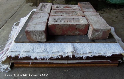 Paper press made from four sheets of marine ply, old towels and bricks
